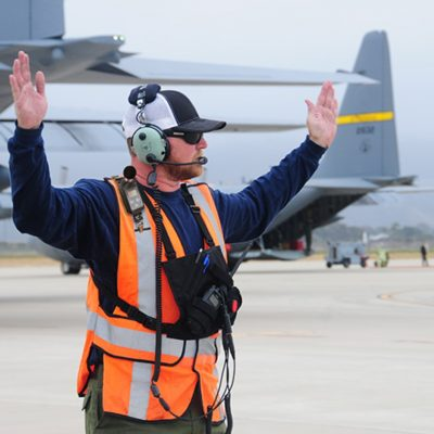 Assistant Tank Manager John Price from Gateway Tanker Base in Mesa, Arizona helps to direct a C-130 taxi out during MAFFS training at the 146th Airlift Wing in Port Hueneme, California on May 4, 2016. Air National Guard and Reserve units from across the U.S. convened for MAFFS (Modular Airborne Fire Fighting Systems)annual certification and training this week to prepare for the upcoming fire season in support of U.S. Forest Service. (U.S. Air National Guard photo by Senior Airman Madeleine Richards/Released)